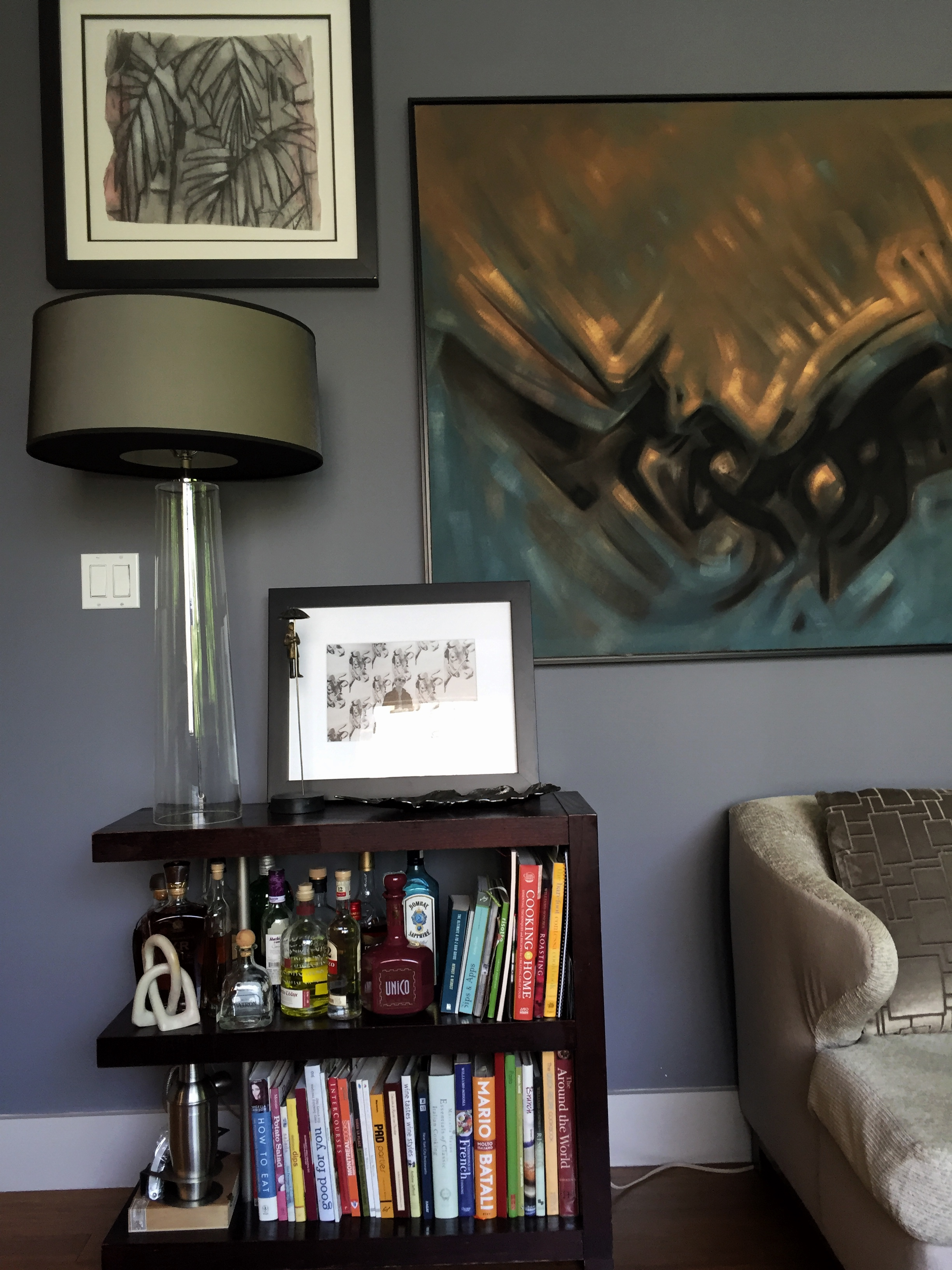 A small bookshelf is handy for entertaining and is topped by a Warhol photo.